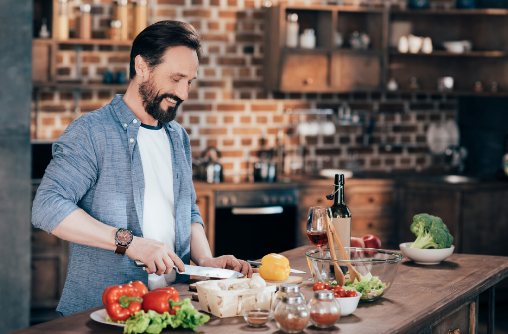 bearded man smiling while chopping vegetables in a modern kitchen with a brick wall