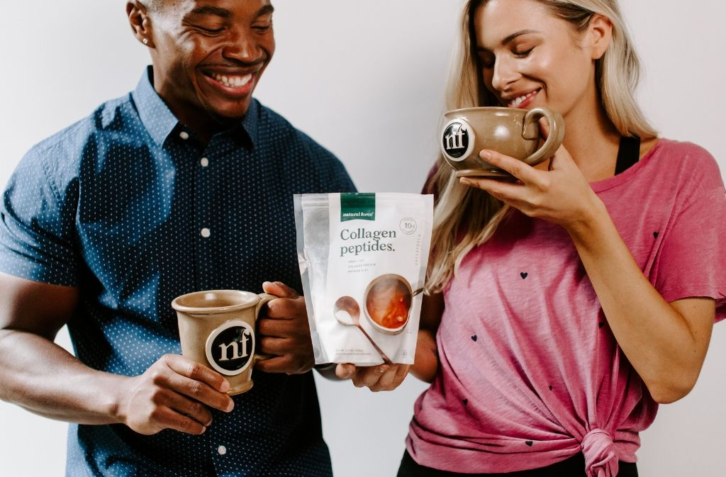 man and woman smiling holding handmade natural force mugs and a bag of natural force collagen peptides