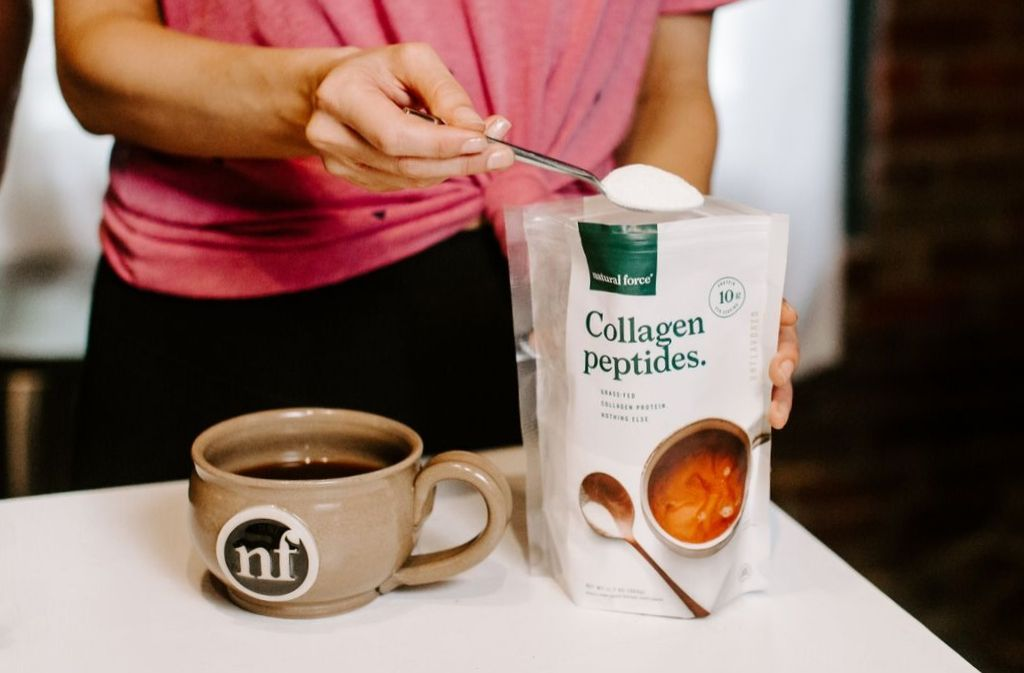 spoon scooping collagen peptides out of a natural force grass fed collagen peptides bag beside a mug of clean coffee