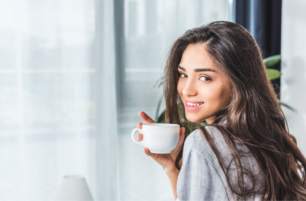 woman with thick shiny hair looking over her shoulder and smiling while holding a cup of coffee