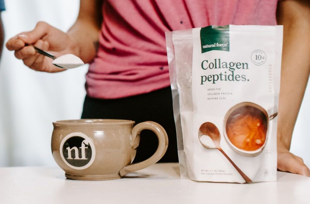 woman adding a spoonful of collagen peptides to a handcrafted natural force mug beside a bag of natural force collagen peptides
