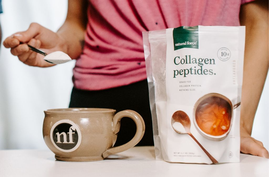 hand holding a spoonful of collagen peptides over a handcrafted natural force latte mug beside a bag of natural force collagen peptides