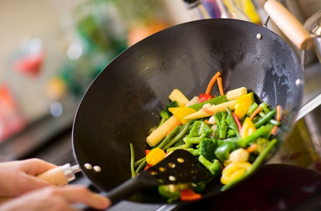 sautéing vegetables with mct oil in a wok