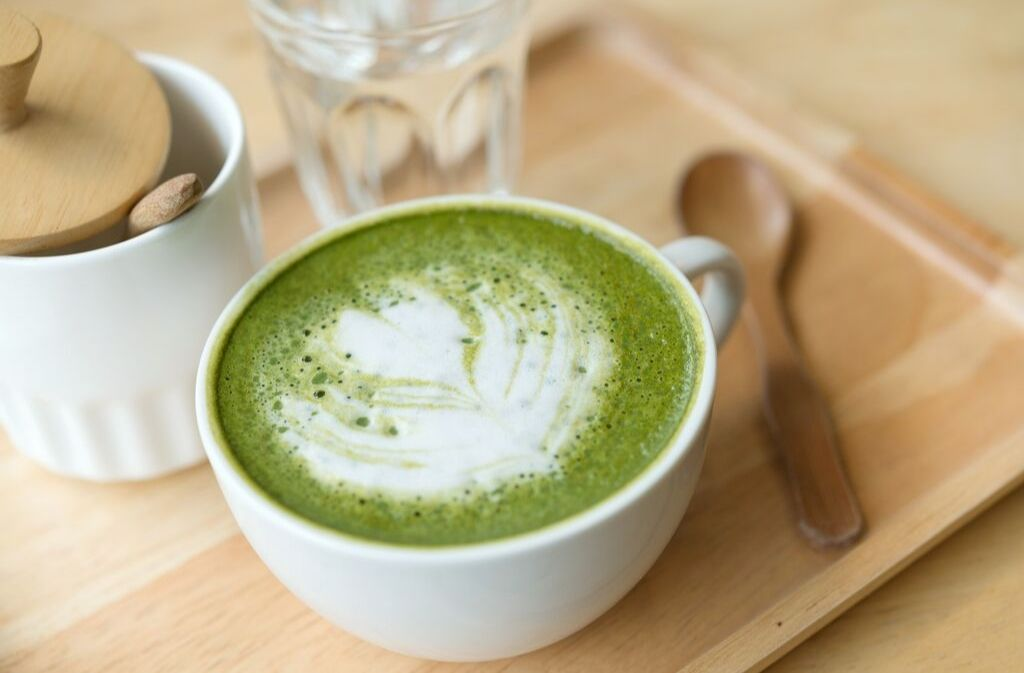 matcha latte in a white mug on a bamboo tray