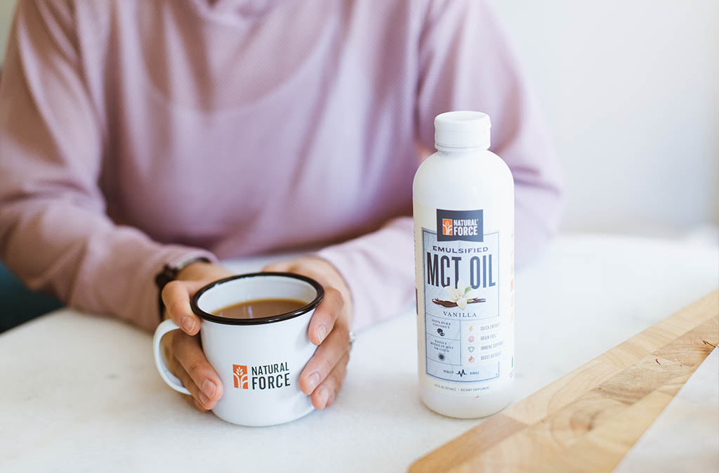 woman's hands around of mug of creamy keto tea beside a bottle of Natural Force Keto Coffee Creamer