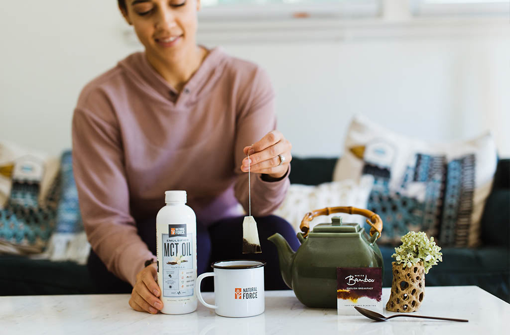 woman holding a tea bag over a mug of creamy keto tea next to tea kettle and Natural Force Keto Coffee Creamer