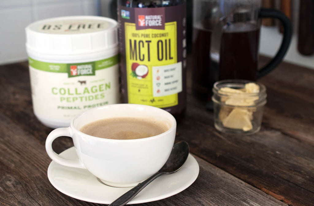 keto coffee in a mug and saucer in front of natural force collagen peptides and natural force mct oil
