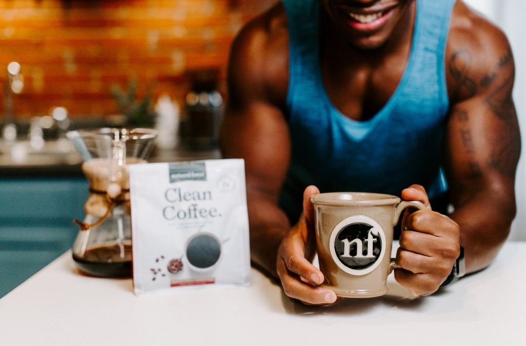 athletic man holding out a handmade natural force mug of dairy free keto coffee beside a bag of natural force clean coffee
