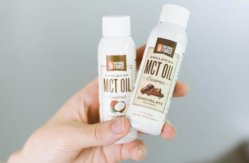 hand holding two mini MCT Creamer bottles - why use mct oil