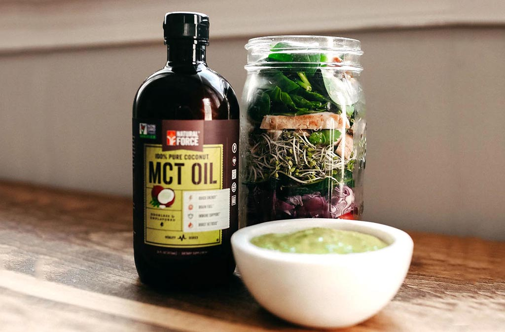 natural force mct oil beside a mason jar salad behind a bowl of keto salad dressing with mct oil