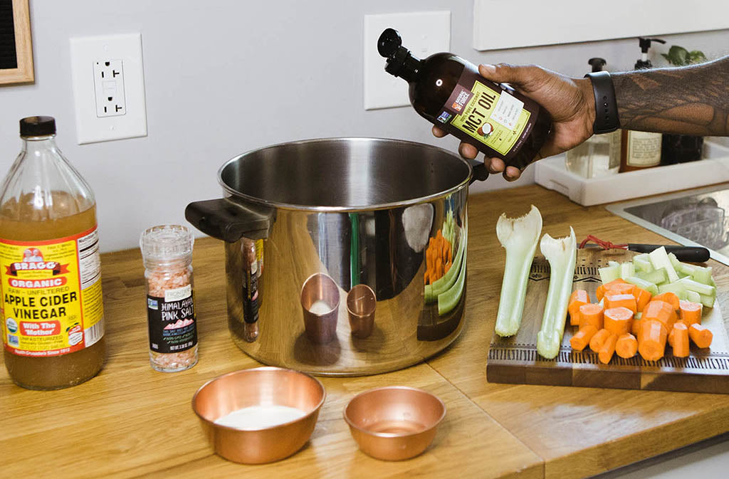 hand pouring natural force mct oil into a stock pot