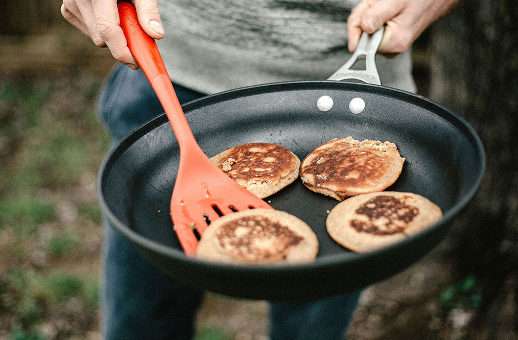 man holding pan with paleo protein pancakes