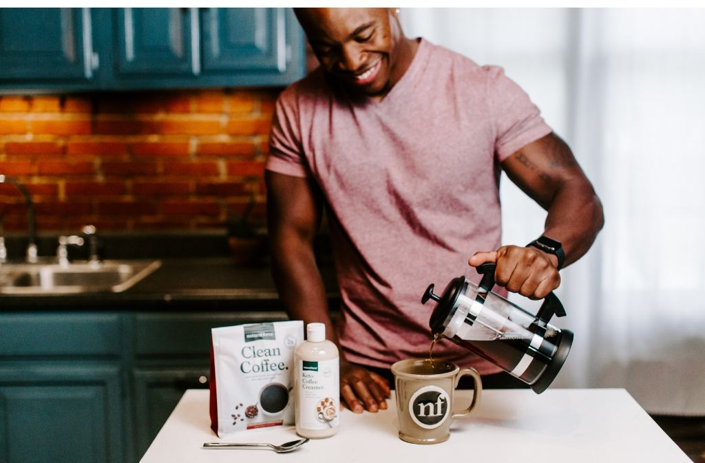 smiling man pouring a French press of coffee into a handmade natural force mug