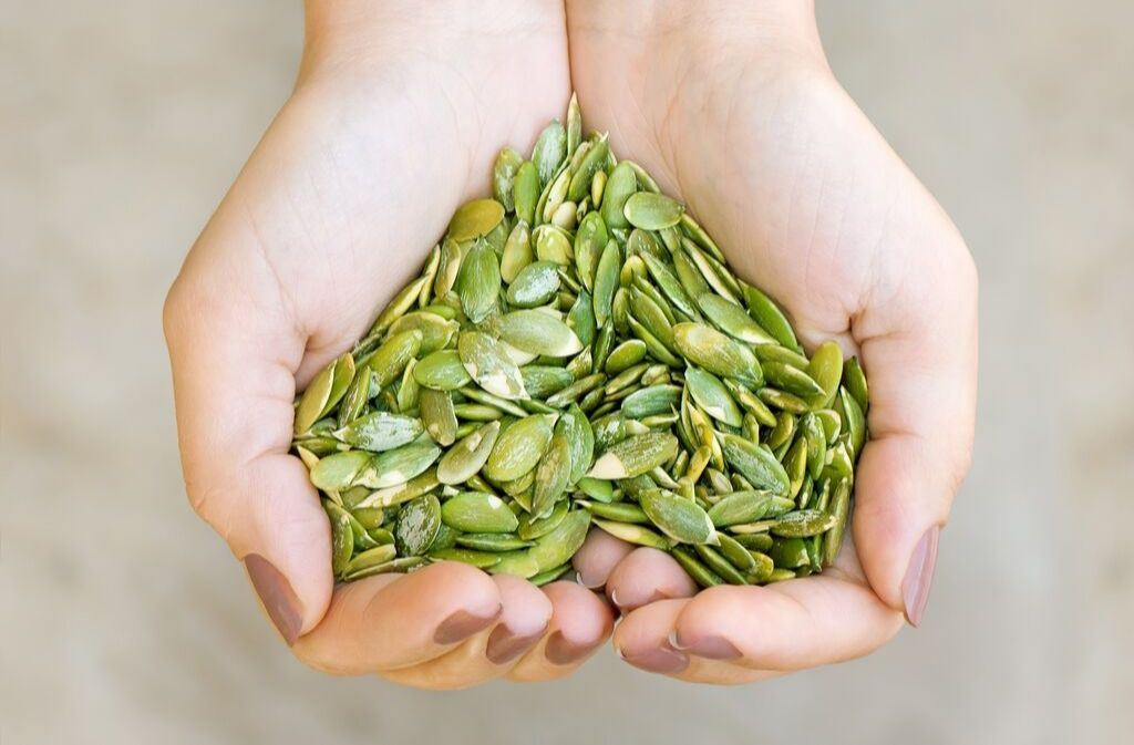 hands holding a heart shaped pile of pumpkin seeds a grain free vegan protein source