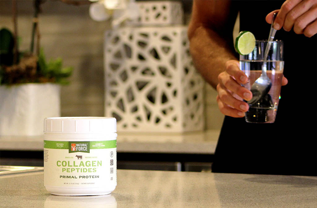 someone stirring a glass of water next to natural force collagen peptides