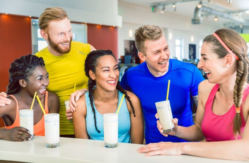 five athletes smiling and laughing while drinking silky smooth protein shakes