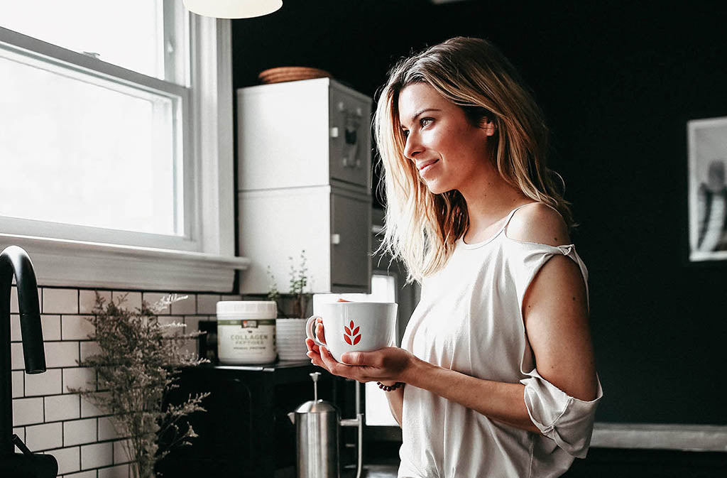 woman holding a white natural force mug looking out the window