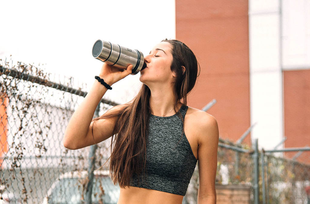 athletic woman in sports bra drinking from a natural force blender bottle