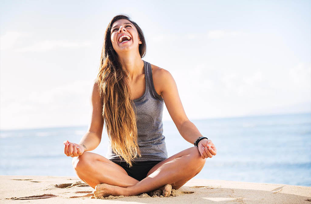 woman in meditation position on a beach laughing