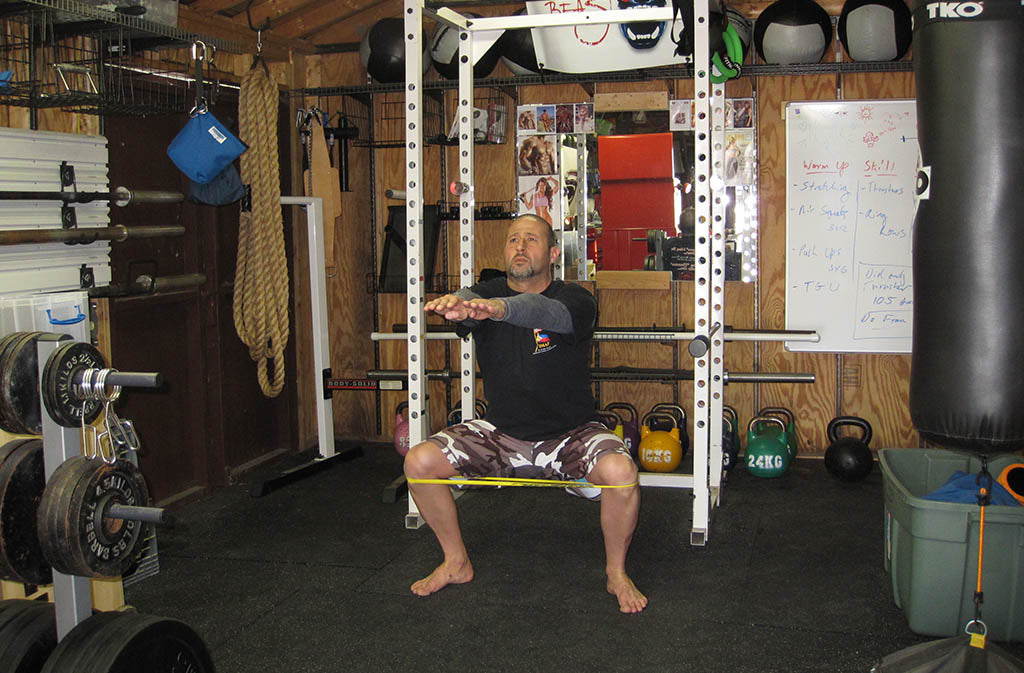 man doing a banded squat
