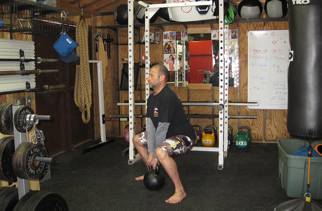 man in position for sumo deadlift squat
