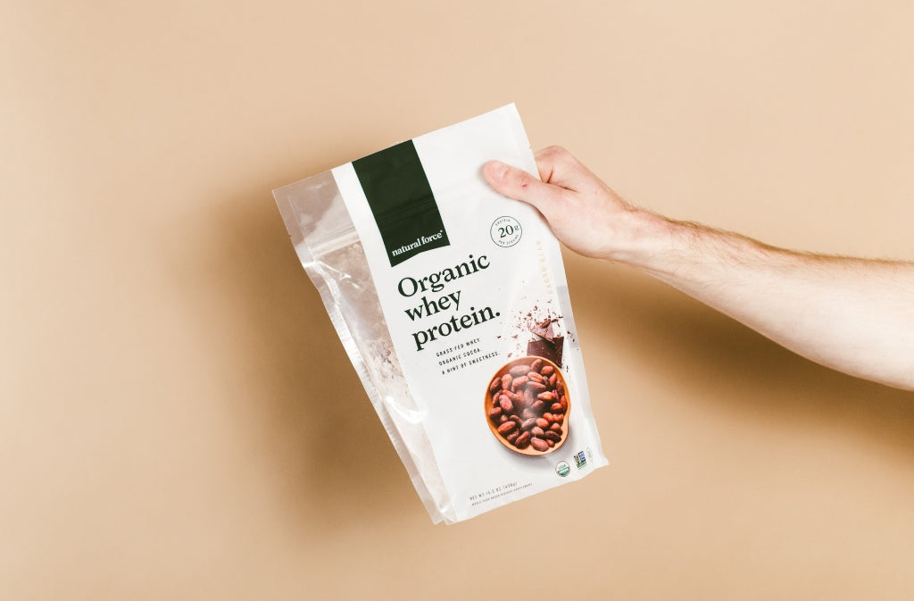 arm holding out natural force organic whey protein