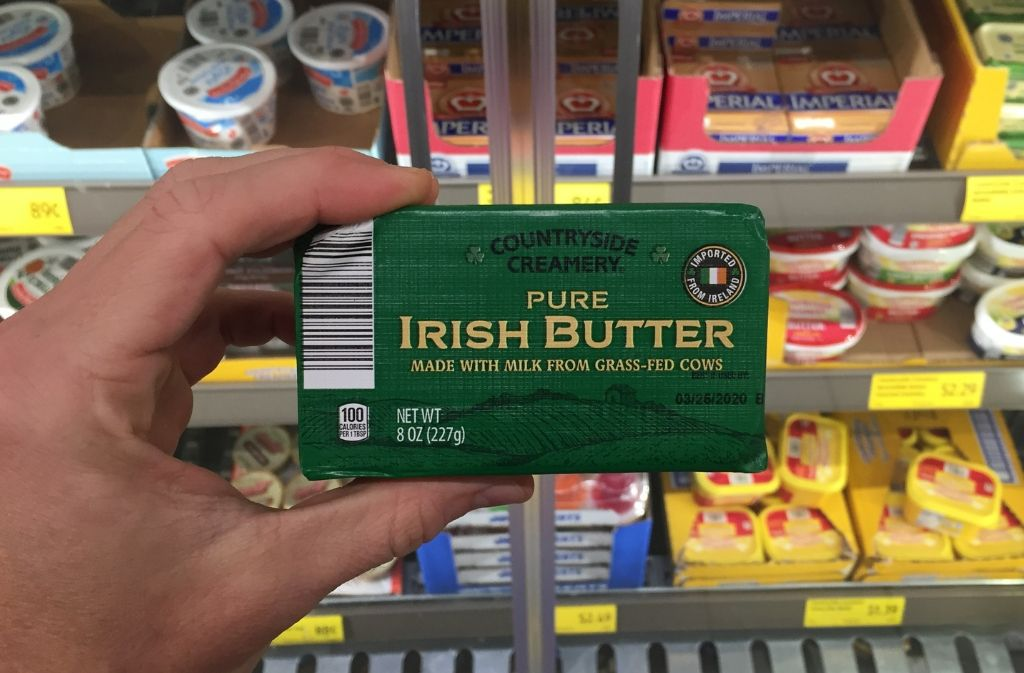 hand holding a package of irish butter