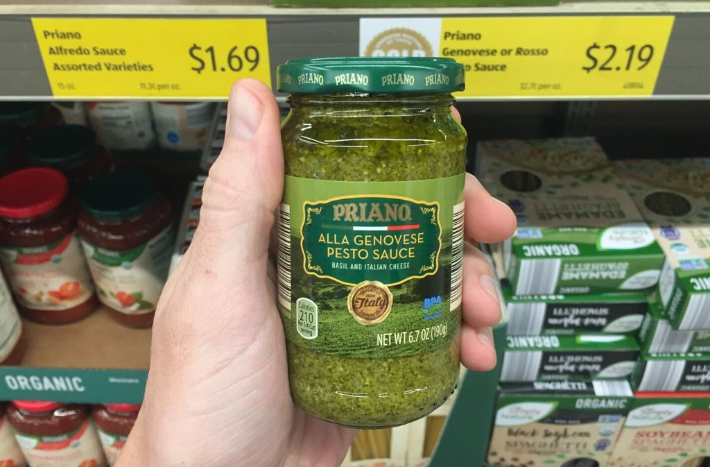 hand holding a jar of pesto