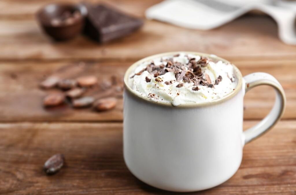 a ceramic mug of keto hot chocolate topped with whipped cream and chocolate shavings on a wood surface