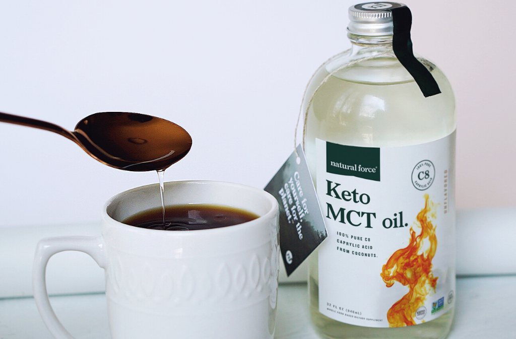 a bottle of natural force keto mct oil beside a white mug of coffee with keto mct oil being poured into it