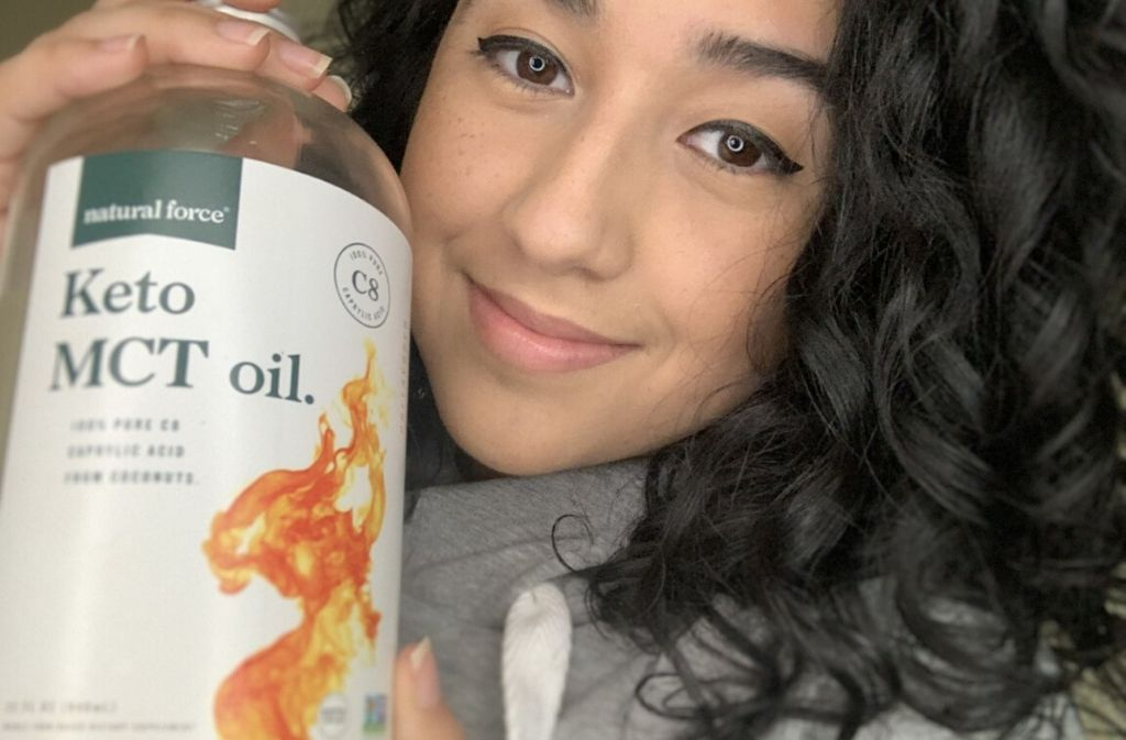 close up of angie hernandez looking at the camera and smiling while holding out a bottle of natural force keto mct oil