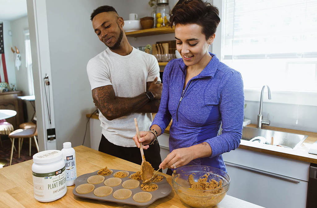 athletic man watching a smiling woman prepare keto pumpkin spice muffins