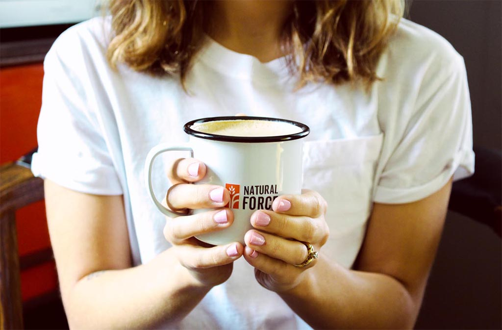 woman in white t shirt holding a natural force mug