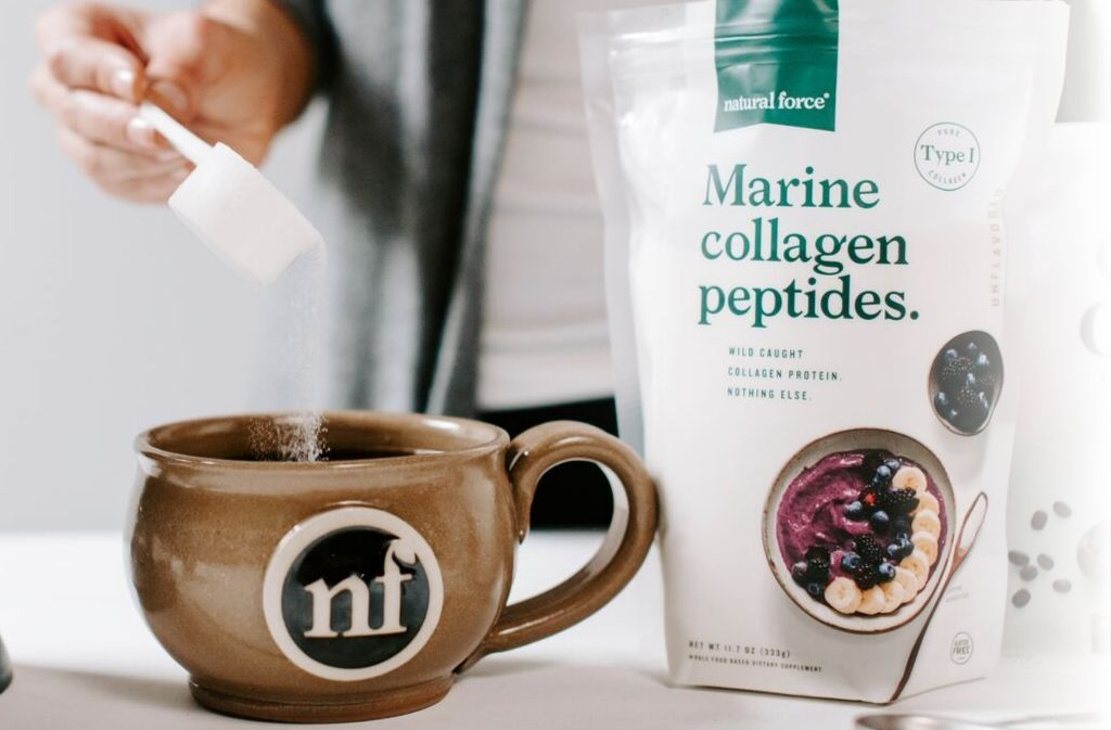 hand pouring marine collagen peptides into a handcrafted natural force mug of keto chai tea latte beside a bag of natural force marine collagen peptides