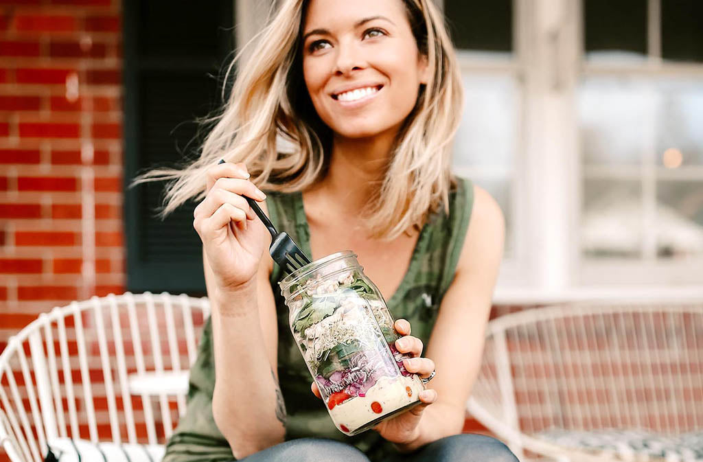 woman smiling eating a mason jar salad