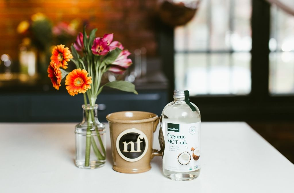 a handmade natural force mug of mct oil in coffee on a counter beside a bottle of natural force organic mct oil and a bouquet of flowers