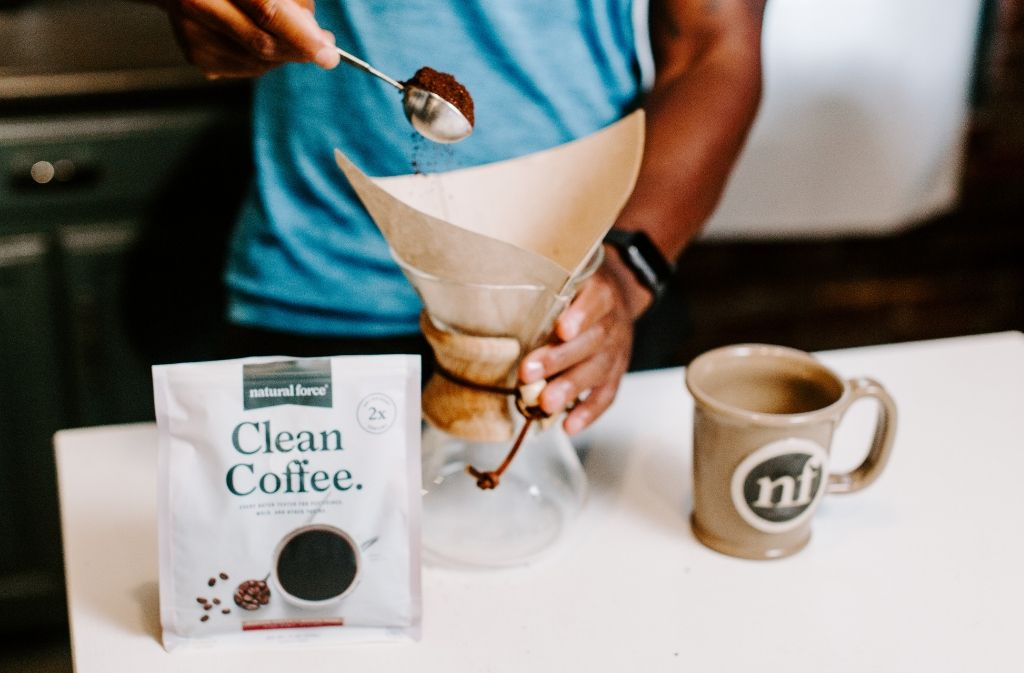 man pouring a tablespoon of ground coffee into a chemex beside a bag of natural force clean coffee and a handmade natural force mug
