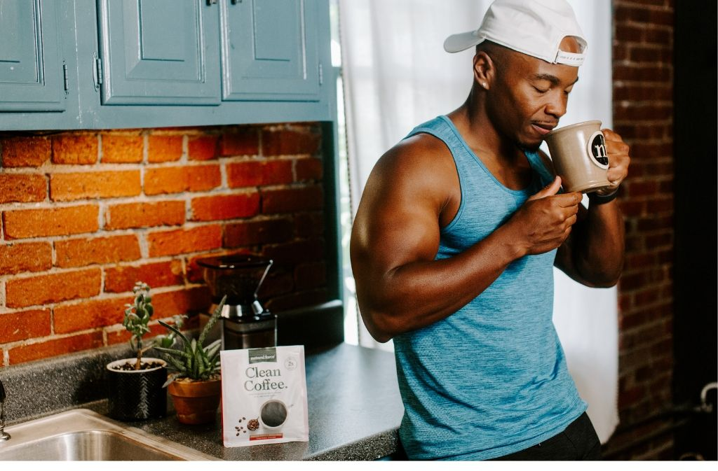 athletic man leaning against a counter smiling as he smells a mug of natural force clean coffee