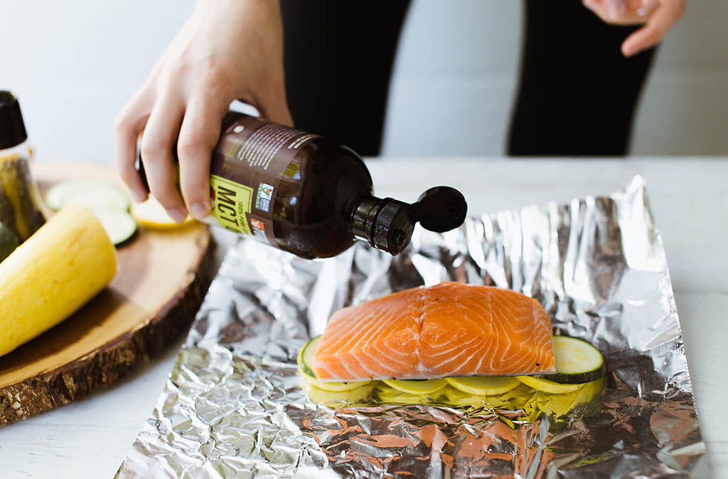 pouring mct oil over a salmon fillet