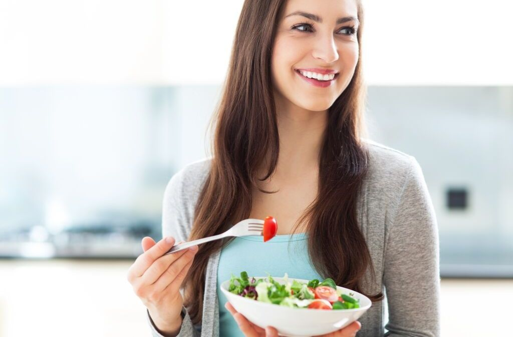 woman looking relaxed while holding a salad and practicing mindful eating