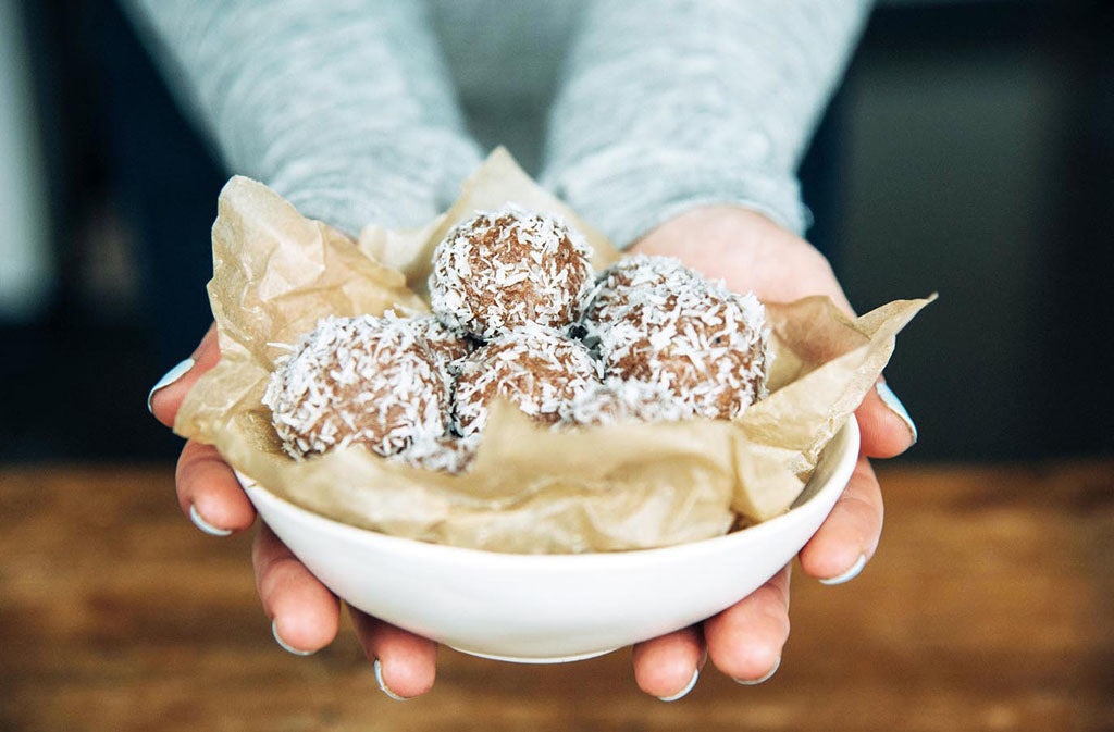 woman's hands holding out a white bowl filled with keto energy bites