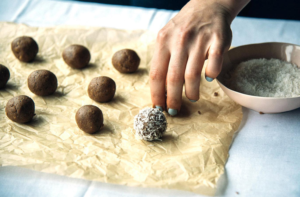hand setting mint chocolate keto energy balls on a piece of parchment paper