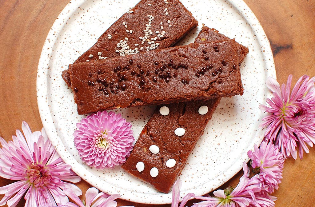 keto chocolate mint protein bars on a white circular plate surrounded by pink flowers