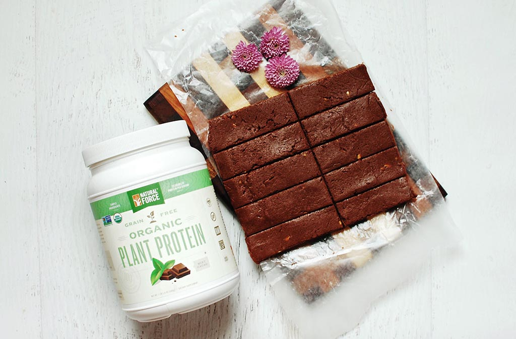 container of natural force organic plant protein next to keto chocolate mint protein bars
