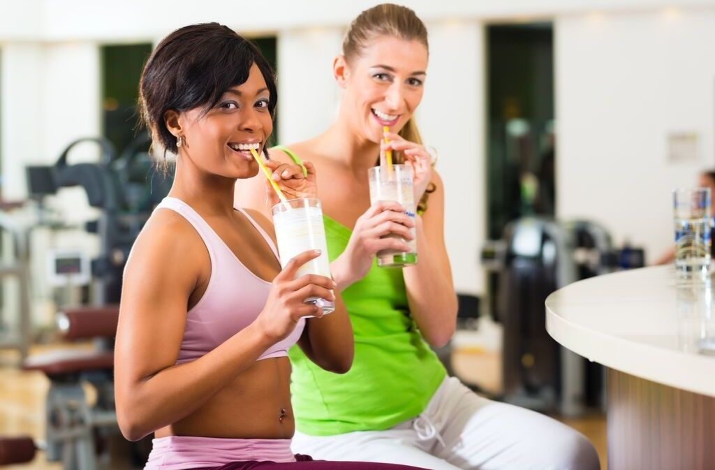 two athletic women smiling while drinking smoothies that mix collagen with protein powder