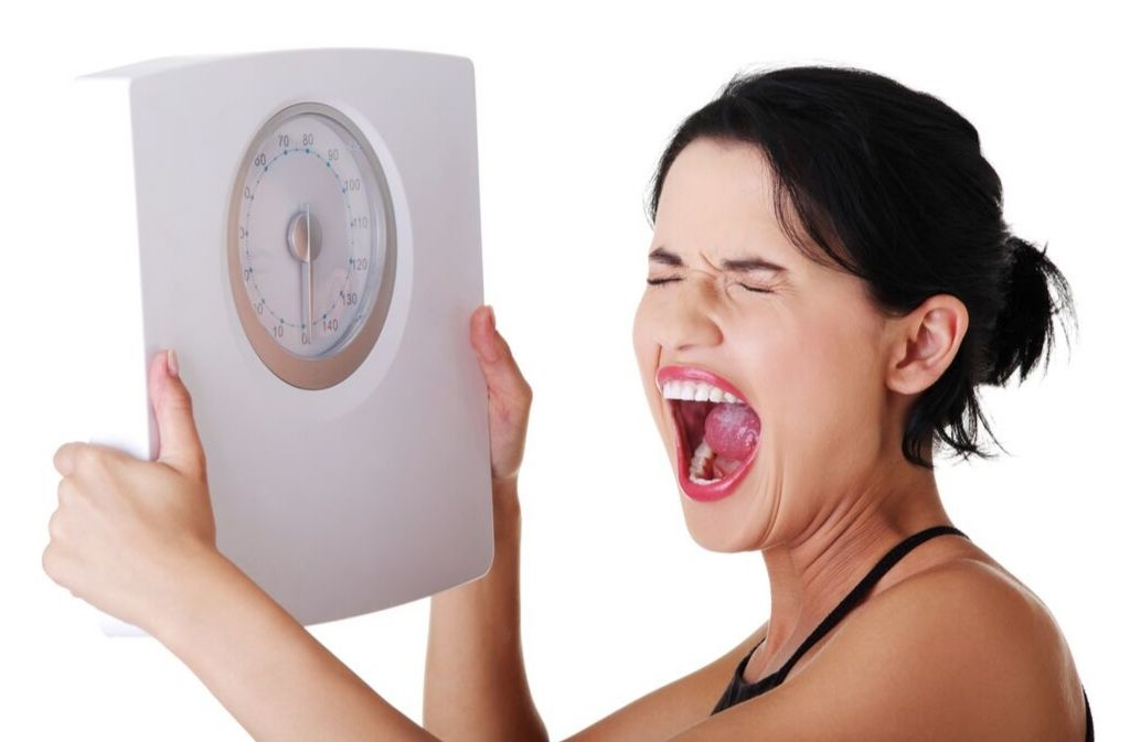 woman who is not losing weight on keto holding a scale and screaming