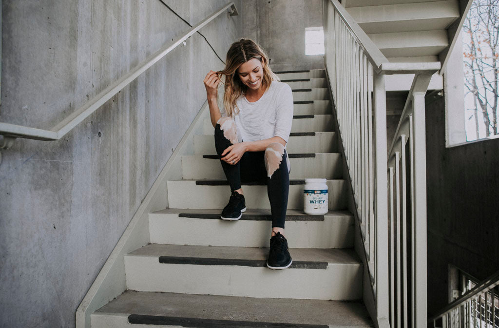 athletic woman sitting on stairs smiling at container of natural force organic whey protein
