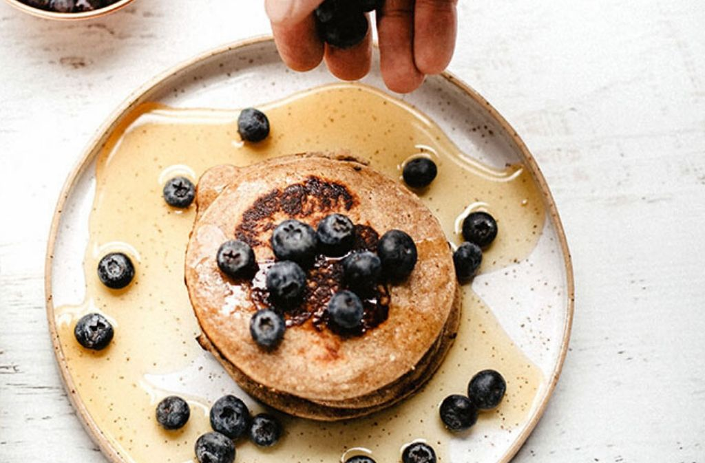 hand dropping blueberries on a plat of paleo protein pancakes