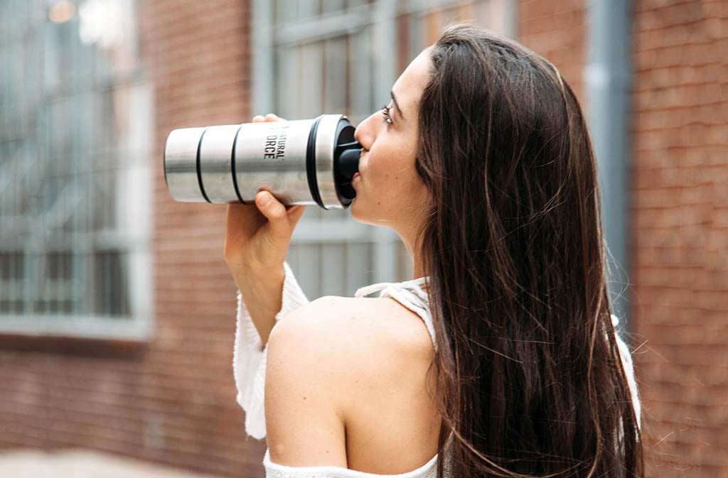 woman drinking from silver natural force blender bottle
