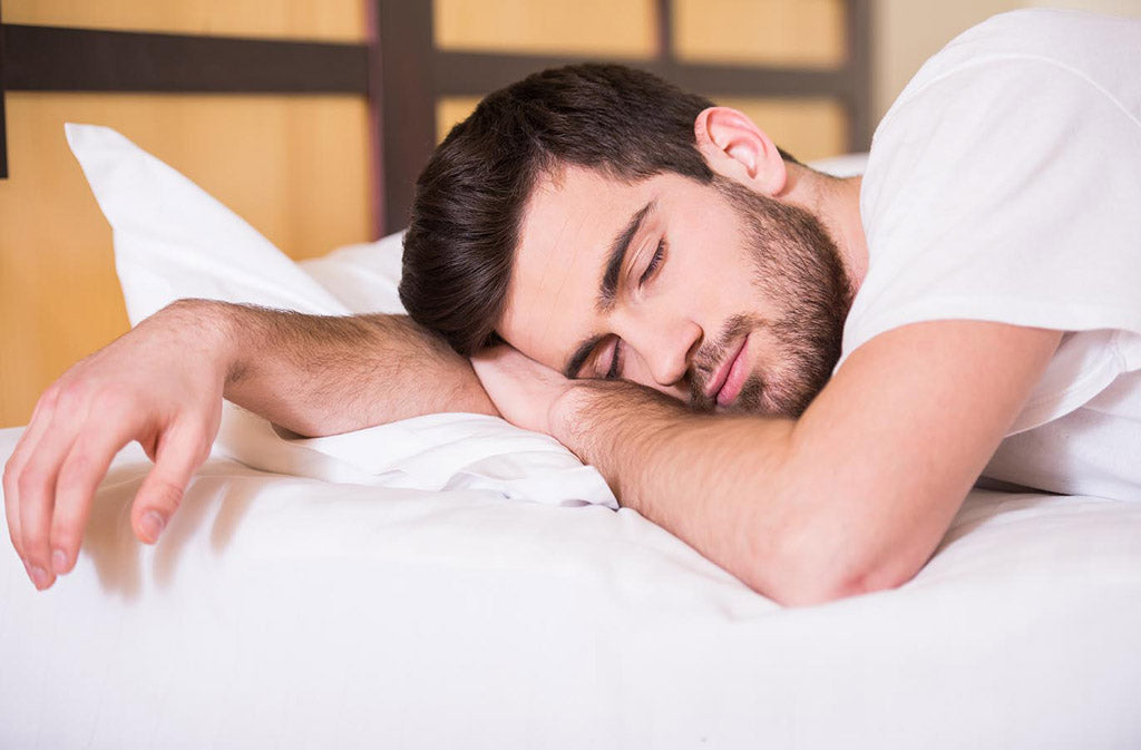 man sleeping on a white bed